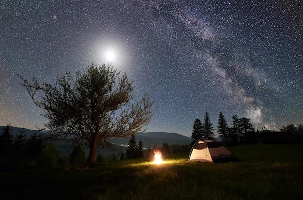 Campamento nocturno en las montañas bajo el cielo estrellado y la vía láctea.