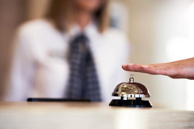Campana del hotel en recepción y recepcionista en