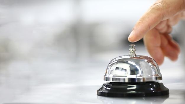 Campana en mostrador para servicio con cliente de dedo para llamada sobre fondo borroso, concepto de servicio