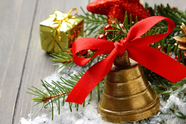 Campana de oro con lazo de cinta de raso rojo