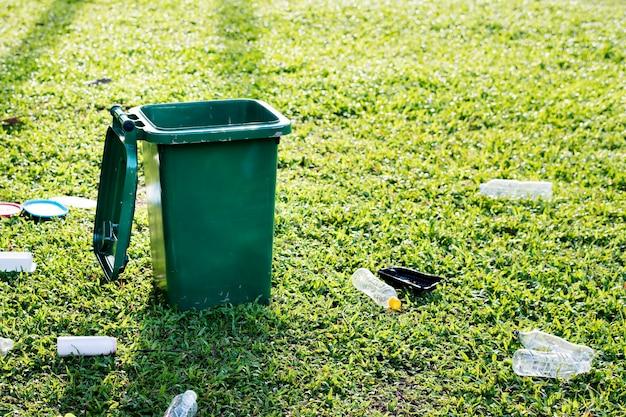 Campaña de reciclaje con papelera verde y botellas de plástico desperdiciadas en el campo
