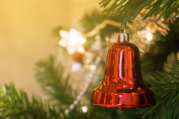 Campana roja colgada en un árbol de navidad
