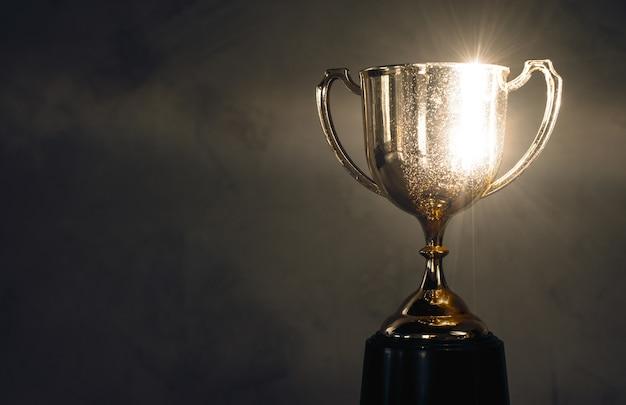 Campeón de oro trofeo colocado en la mesa de madera