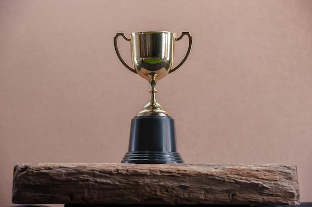 Campeón de oro trofeo en mesa de madera.