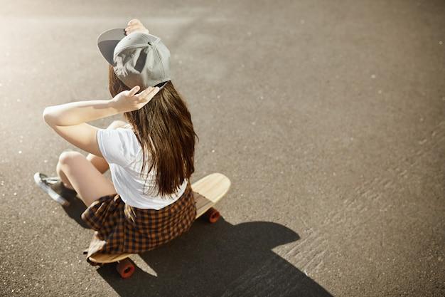 Campeona de skate femenina sentada en su longboard con sombrero en un día soleado en un entorno urbano.