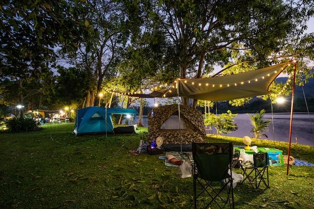 Camping y carpa en parque natural al atardecer.