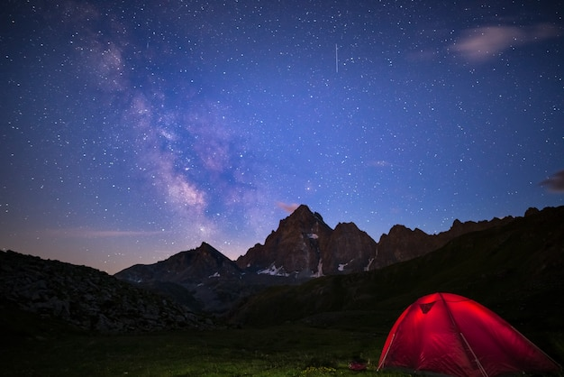 Camping bajo el cielo estrellado y la vía láctea a gran altitud en los alpes.