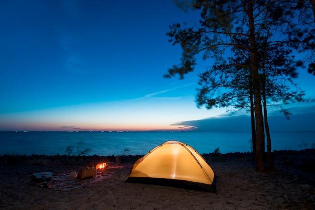 Camping por la noche junto al lago.