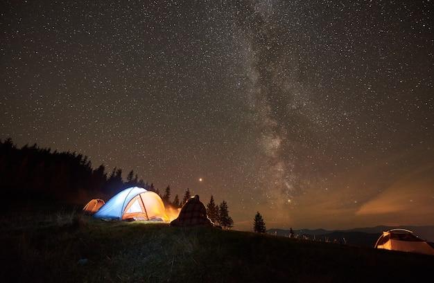 Camping nocturno con gente alrededor de una fogata bajo el cielo estrellado nocturno.