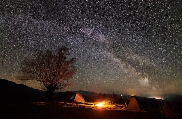 Camping nocturno en el valle de la montaña bajo un cielo estrellado.