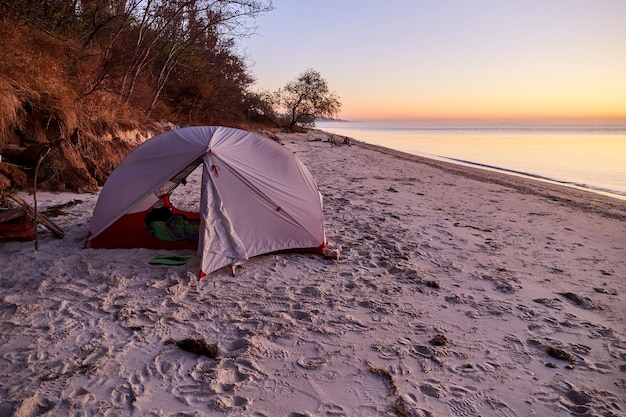 Camping en la playa del mar. salida del sol en la playa de arena del mar de azov. idílica escena de otoño