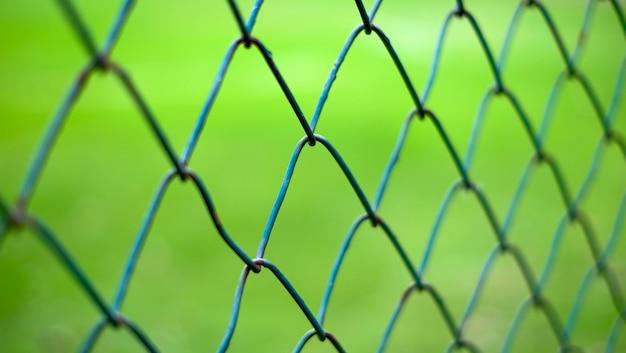 Campo de césped detrás de la valla verde de malla