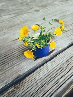 Campo de flores amarillas en florero azul