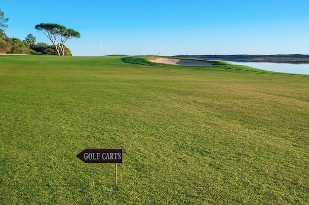 Campo de golf y una señal para los carros de golf.