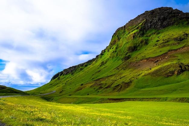 Campo de hierba cerca de una montaña cubierta de hierba bajo un cielo nublado
