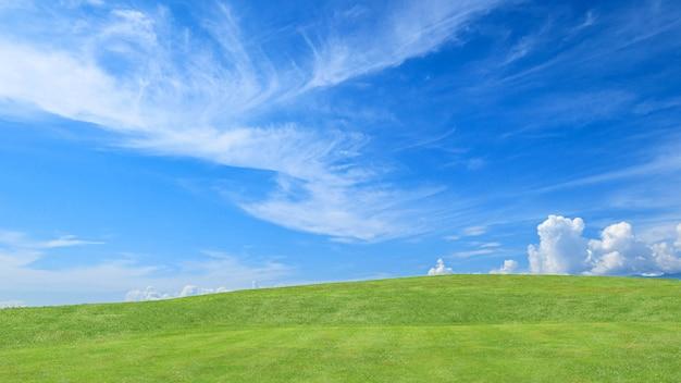 Campo de hierba verde en pequeñas colinas y cielo azul con nubes