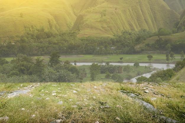 Campo de pradera con río y colinas.