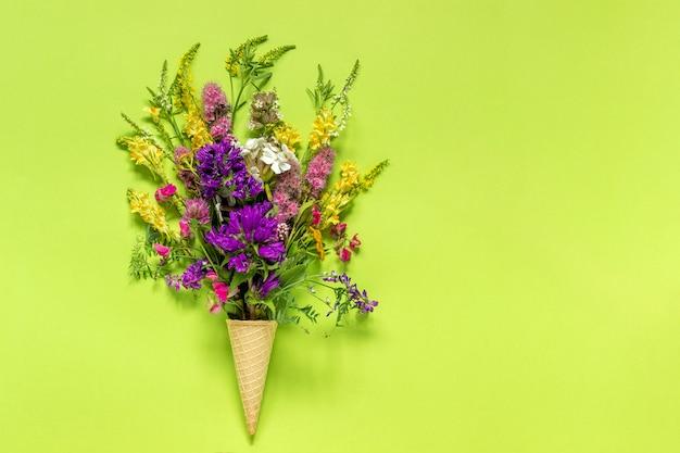 El campo del ramo coloreó flores en cono de helado de la galleta en fondo del libro verde
