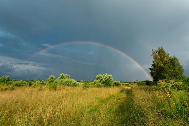 Campo soleado justo después de la lluvia con el doble arco iris en el cielo azul oscuro.