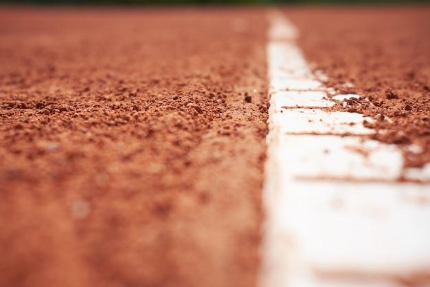 Campo de tenis de arena roja con fondo de línea blanca cerca