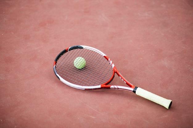 Campo de tennies de alto ángulo con pelota y raqueta