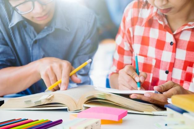 El campus de los estudiantes jóvenes ayuda al amigo a ponerse al día y aprender.