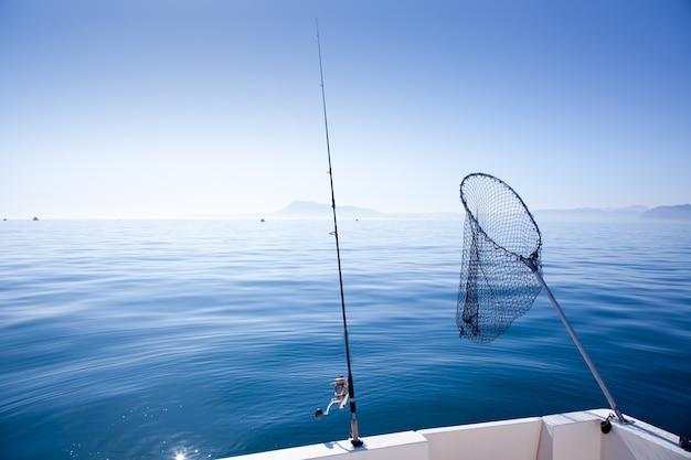 Caña de pescar en barco y red de aterrizaje en el mar