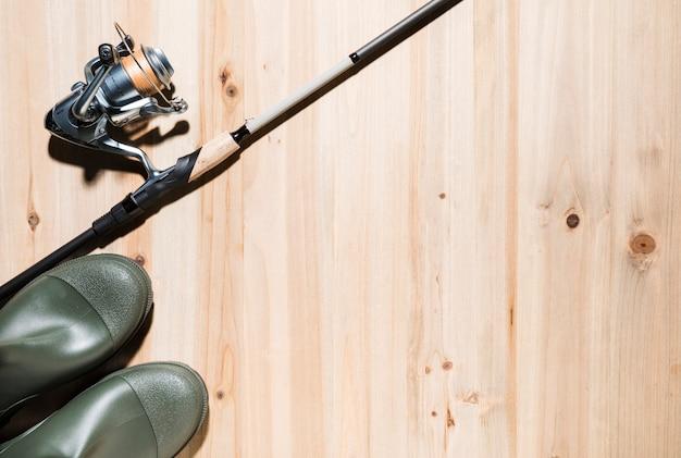 Caña de pescar y carrete de pesca con botas wellington en superficie de madera.