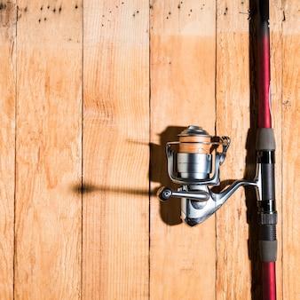 Caña de pescar con carrete de pesca en el escritorio de madera