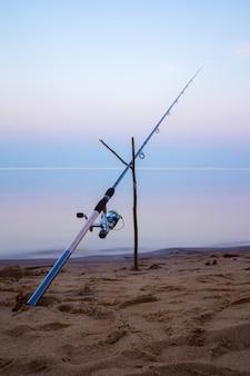 Caña de pescar en la orilla de la playa de arena al atardecer.