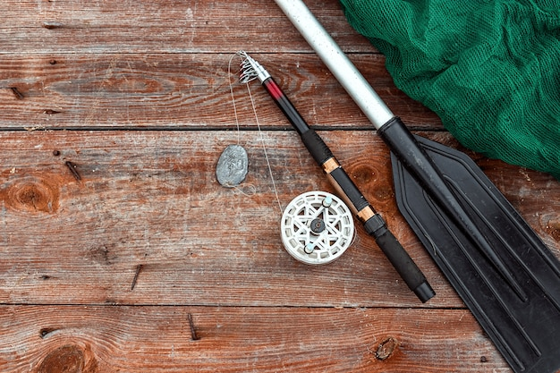 Caña de pescar con paleta y red de pesca en una vista superior de madera vacaciones de pesca hobby