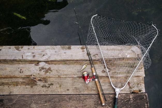 Caña de pescar y red de pesca en el borde del muelle de madera