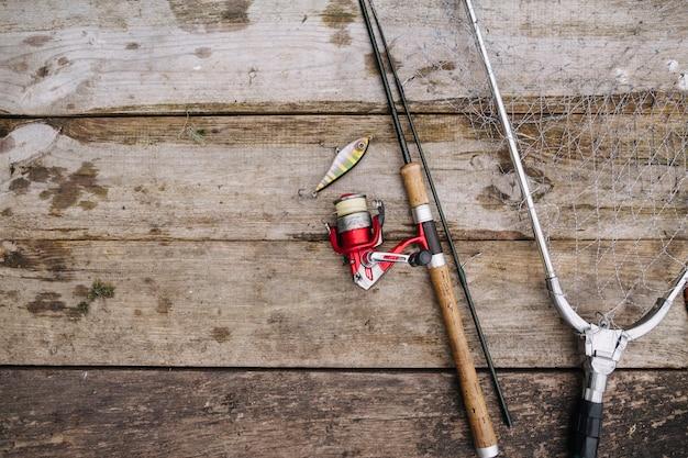 Caña de pescar con señuelo y red en el muelle de madera