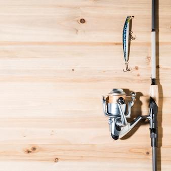 Caña de pescar con señuelo sobre tabla de madera.
