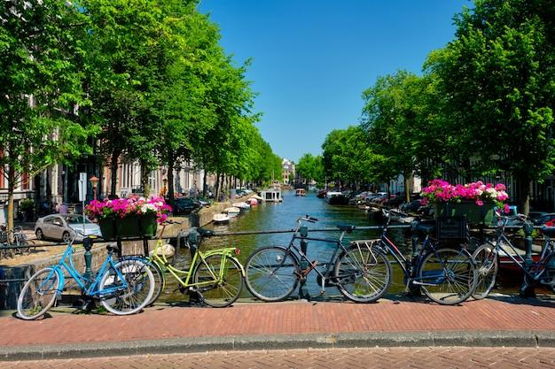 Canal de amsterdam con barcos y bicicletas en un puente