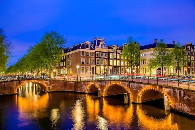 Canal de amsterdam con casas holandesas típicas durante la hora azul crepuscular en holanda, países bajos.