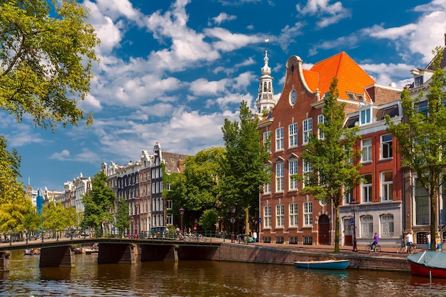 Canal de amsterdam, puente, iglesia y casas típicas en el día soleado de verano, holanda, países bajos.