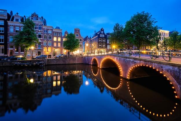 Canal de amterdam, puente y casas medievales en la noche