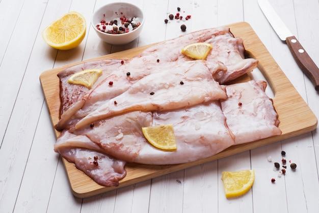 Canal de calamar crudo con especias y limón listo para cocinar en la mesa.