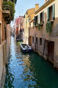 Canal estrecho tradicional con barcos en venecia, italia. verano