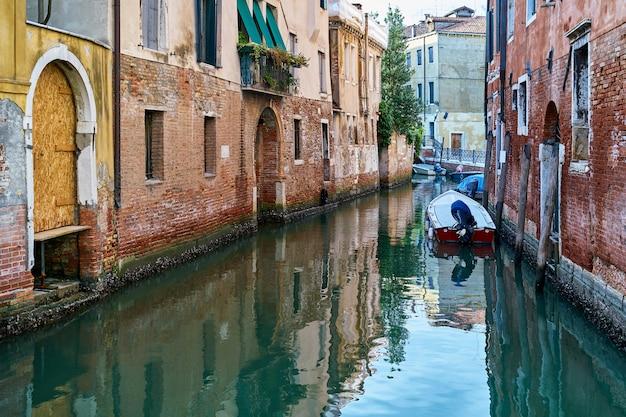 Canal estrecho tradicional con barcos en venecia, italia