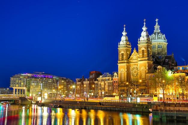 Canal y la iglesia de san nicolás en amsterdam en el crepúsculo, países bajos