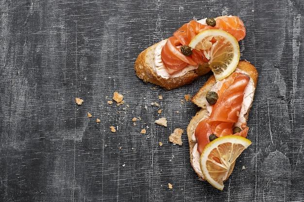 Canapé con salmón ahumado y queso crema, enfoque selectivo, vista superior