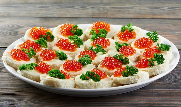Canapés con mantequilla, caviar rojo y perejil, servidos para catering en restaurante o buffet. bueno para bebidas alcohólicas ligeras y otras comidas.