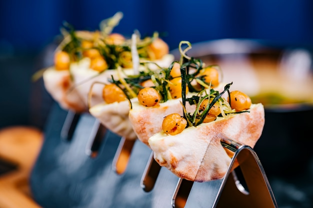 Canapés con rúcula de bayas fritas en vista lateral de pan
