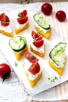 Canapés vegetarianos de polenta con queso, verduras y berros. estilo rústico