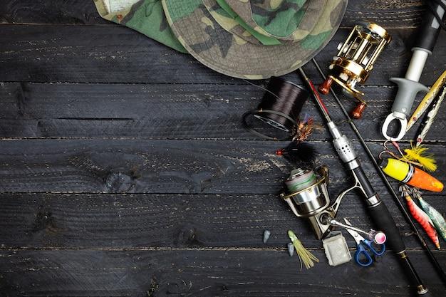 Cañas de pescar y carretes, aparejos de pesca en el fondo de madera negro