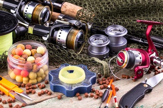 Cañas de pescar y spinning en la composición con accesorios para pescar en la superficie vieja de la mesa