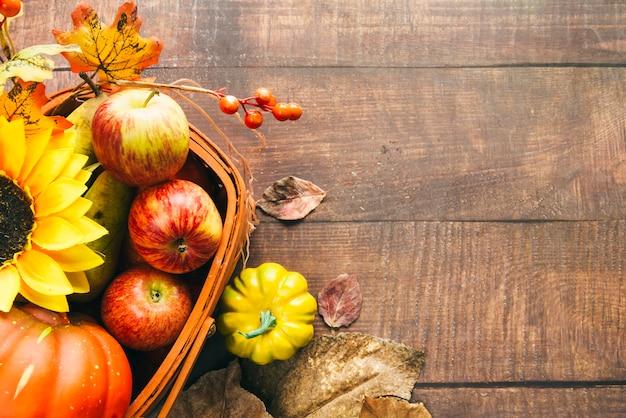 Canasta con cosecha otoñal y girasol sobre mesa.