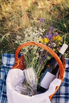 Canasta de frutas y vino en una tela escocesa durante un picnic romántico